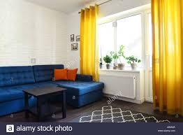 clean family room with blue couch white brick wall and yellow