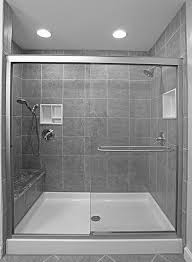 small bathroom with glass shower stall and gray ceramic wall panel brown stained oak wood bathroom