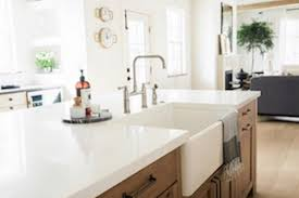 wood kitchen cabinets with white countertops white countertops with an inset farmhouse sink sit atop