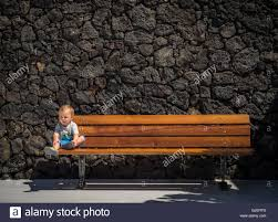 small little boy resting on a wooden bench on a summer day