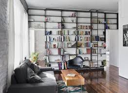 furniture ladder bookcase with grey sofa and black chair on