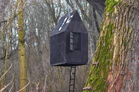 black flying house creepily suspended from old railroad bridge