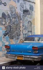old blue pontiac car in cuba in front of murals on wall at havana stock photo old blue pontiac car in cuba in front of murals on wall at havana cuba west indies caribbean central america