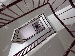 looking up winding stairwell with geometric pattern stock photo