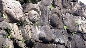 stone wall decoration depicting face of hindu mythological
