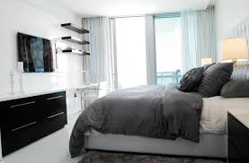 big white bed with gray duvet and pillows toward the mounted flat