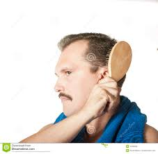 man brushing his hair in the bathroom mirror stock photography
