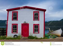 white cottage with red door in canada stock photo image 74324390