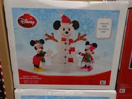 mickey and minnie decorating the snowman