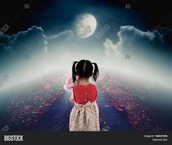 halloween sky background back view of lonely child with doll sad gesture on pathway with a