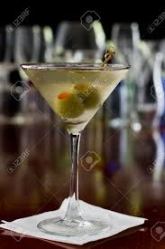 dry vermouth color dirty martini chilled and served on a busy bar top with a shallow