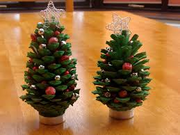 a little christmas tree craft project with fir cones paint and