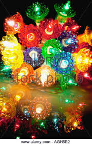 bundle of coloured christmas tree lights illuminated on white