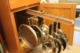 traditional kitchen with pull out rack hanging pots pans and pot