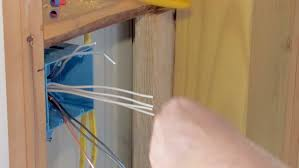 electrician wiring wall outlet box in new construction stock
