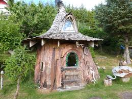 someone transformed this tree stump into a fancy hobbit house