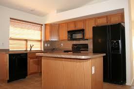 oak kitchen cabinets with black appliances home design ideas