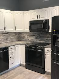 do white cabinets go with black appliances stackstone backsplash black stainless appliances white