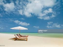 Lounge Chair Umbrella Couple On Beach Laying On Lounge Chairs Under Beach Umbrella Stock