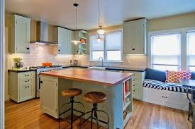 White Kitchen Cabinets With Black Island by Black Countertop White Island With Open Shelves Brown Wooden Chair