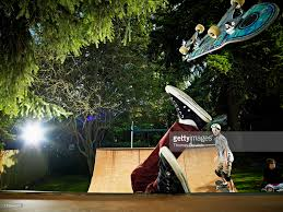 skater falling off skateboard on backyard halfpipe stock photo