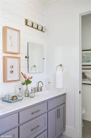 gray bathroom vanity and white counter tops with shiplap feature