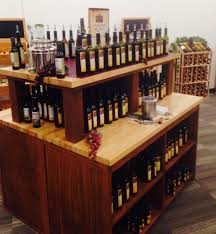 rustic wood retail store product display fixtures shelving double sided fusti bar riser table display rustic wood olive oil butcher block