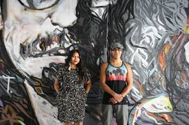 four native artists create murals for oklahoma city s bricktown hatfield and grounds pose in front of their mural called strength of the woman