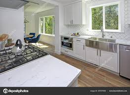 white kitchen cabinets with marble counters remodeled kitchen with white cabinets marble countertops herringbone backsplash and wide plank hardwood floors 207577544