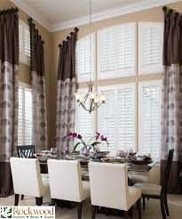 timeless elegance in the dining room two story windows covered