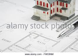 model home pencil ruler compass and key resting on custom house