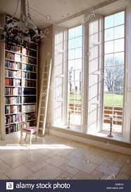 floor to ceiling bookshelves and tall windows in white library