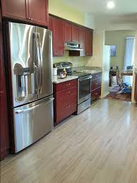 Kitchen Floors With Cherry Cabinets Grey Hardwood Floors Accent A Modern Kitchen With Cherry Cabinets