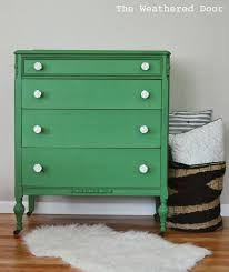 a mossy green dresser with white rose knobs the weathered door