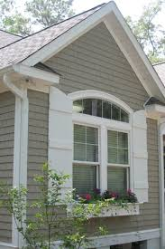 cottage exterior of home with arched window and country french