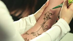 an indian lady does a henna tattoo on a client u0027s hand and wrist