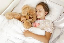 big teddy girl sleeping and hugging big teddy at bed