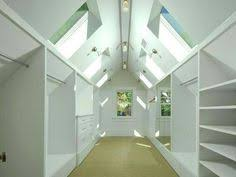 walk in attic closet features a sloped ceiling lined with rustic