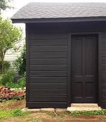 Black Exterior Gloss Paint - the black garage recedes allowing the garden and the white greek