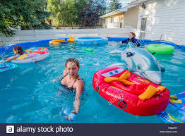 girls in above ground backyard swimming pool stock photo royalty