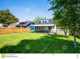 backyard of blue american house with well kept lawn around stock