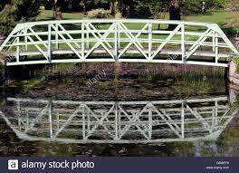white wrought iron single span arch bridge over a pond botanic