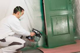 spray painting a door using graco airless spray gun or paint