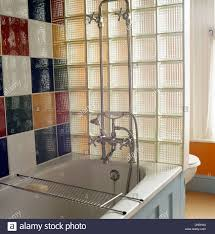 modern bath taps and shower attachment stock photo royalty free bath shower attachment colorful tiles above bath with chrome shower attachment behind glass block wall dividing bath from toilet