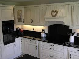 black painted glass backsplash with white cabinets kitchen