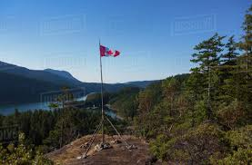 a canadian flag pole on top of a mountain in desolation sound