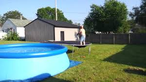 bald guy tries to jump from trampoline to pool jukin media