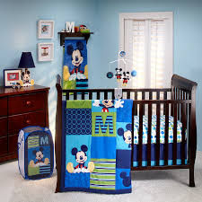brown polished wooden baby crib with mickey themes of blue bedding