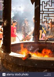 Burning Pit Of Fire - incense sticks burn on the edge of a fire pit at lingyin temple in
