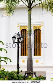 white stucco building with ornate gold decorated windows a
